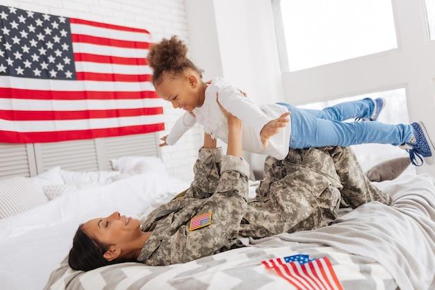 Voe como um pássaro. mãe forte e charmosa segurando o filho nos braços enquanto está deitada na cama e aproveitando as férias em casa