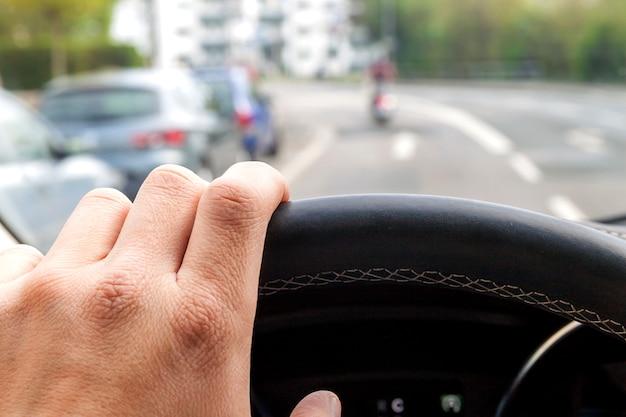 Volante com motorista mão no interior do carro moderno, com vista para a rua