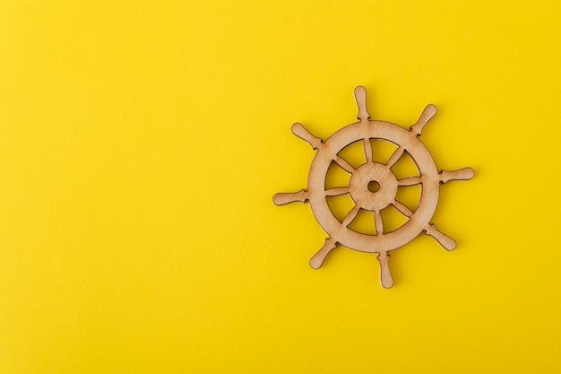 Volante de madeira em fundo amarelo. tema marinho. gestão de iates.