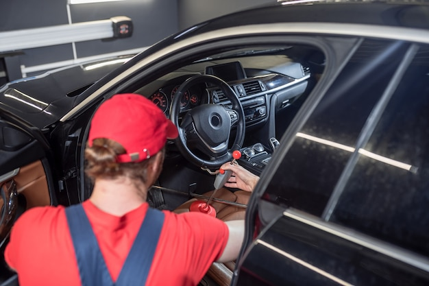 Volante, serviço. homem com boné vermelho consertando volante de carro em oficina mecânica
