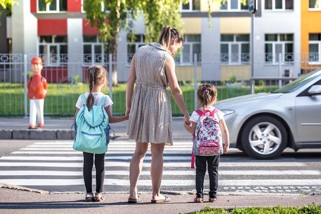 Volta ao conceito de educação escolar com crianças menina, alunos do ensino fundamental, carregando mochilas, indo para a aula