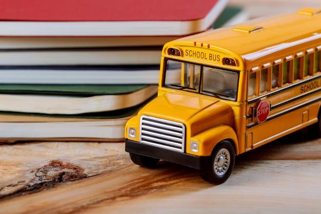 Volta ao conceito de escola, caneta colorida, caderno, fundo de madeira de ônibus escolar de brinquedo amarelo