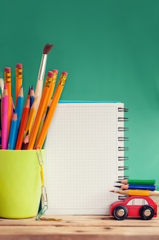 Volta ao conceito de escola. carro vermelho em miniatura, carregando um lápis colorido e maçã vermelha na mesa de madeira