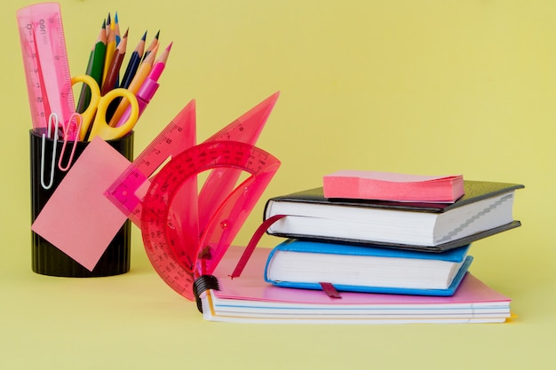 Volta ao conceito de escola, com espaço para texto. copie o espaço. material de escritório escolar. mesa criativa com artigos de papelaria coloridos. clipe de papel colorido. material escolar em fundo amarelo. mesa de escritório