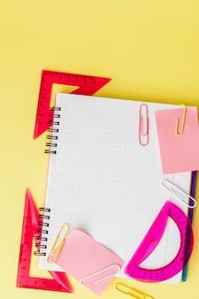 Volta ao conceito de escola, com espaço para texto. vista do topo. copie o espaço. material de escritório escolar. mesa criativa com artigos de papelaria coloridos. clipe de papel colorido. material escolar em fundo amarelo. mesa de escritório