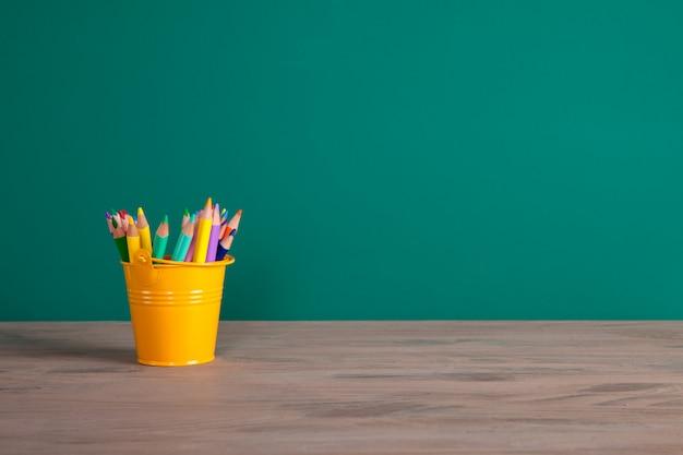 Volta ao conceito de escola com lápis coloridos. quadro negro com espaço para texto