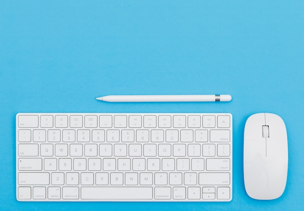 Volta ao conceito de escola com lápis, teclado, mouse sobre fundo azul plana leigos.