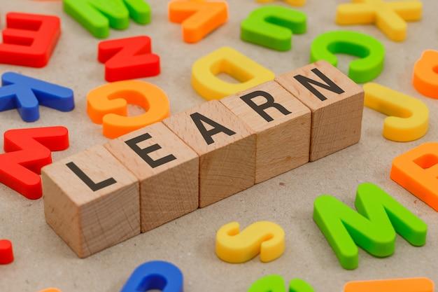 Volta ao conceito de escola com letras do alfabeto, cubos de madeira na vista de alto ângulo de papel.