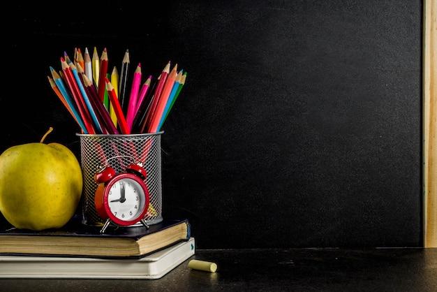 Volta ao conceito de escola com livros despertador lápis de cor lousa fundo