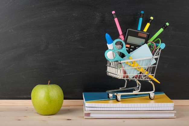 Volta ao conceito de escola com material escolar e maçã verde no fundo do quadro-negro