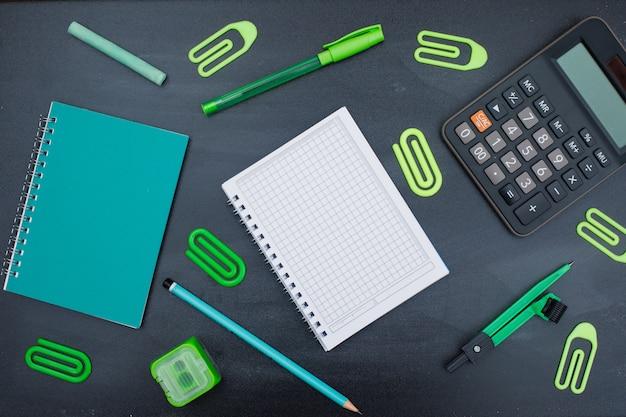 Volta ao conceito de escola com material escolar em fundo cinza plana leigos.