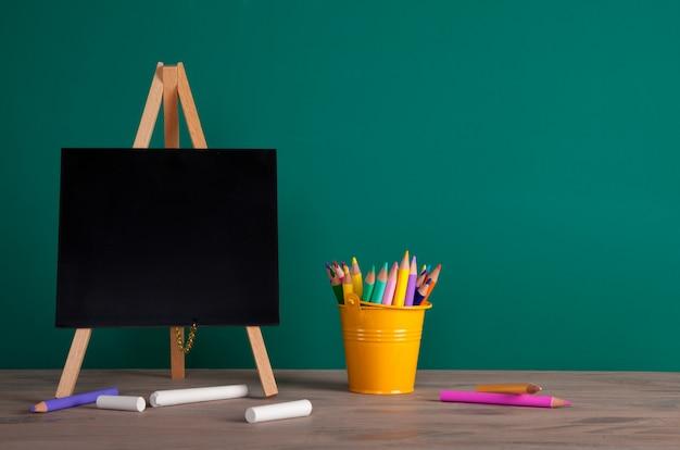 Volta ao conceito de escola com material escolar. lápis coloridos e quadro-negro com espaço de cópia