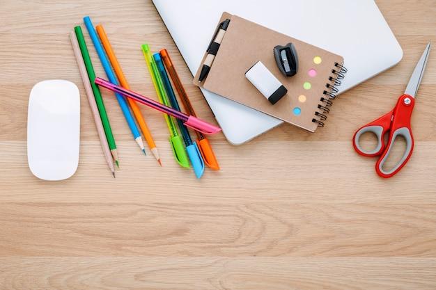 Volta ao conceito de escola com material escolar na mesa de madeira.