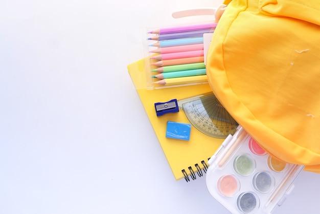 Volta ao conceito de escola com mochila amarela e fornecedores de escola na mesa.