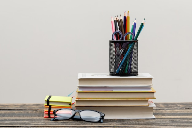 Volta ao conceito de escola com óculos, itens de escola na vista lateral da parede de madeira e branco.