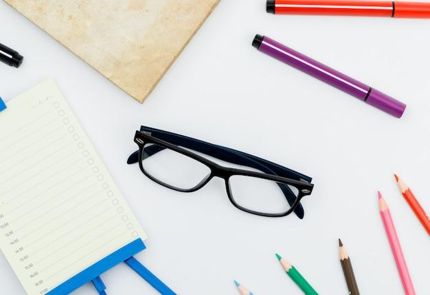 Volta ao conceito de escola com óculos, material escolar, planejador diário na mesa branca plana leigos.