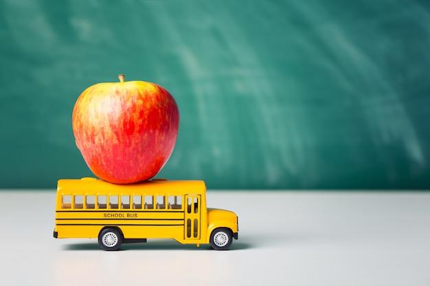 Volta ao conceito de escola com ônibus amarelo e maçã