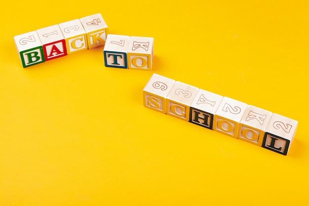 Volta ao conceito de escola. cubos alfabéticos de madeira coloridos em amarelo brilhante