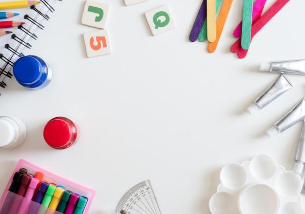 Volta ao conceito de escola e artista garoto conceito com livro de desenho, giz de cera, lápis de cor, cor de cartaz e papelaria escolar