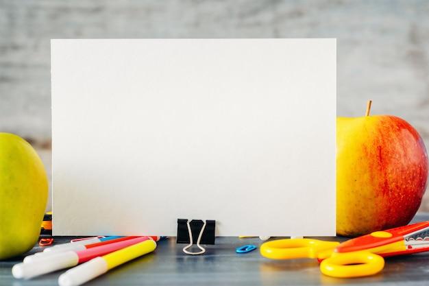 Volta ao conceito de escola. folha em branco branca com duas maçãs e material escolar na mesa