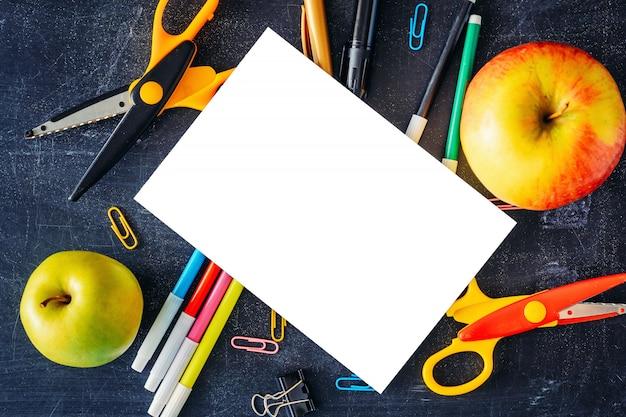 Volta ao conceito de escola. folha em branco branca isolada com duas maçãs e material escolar na vista superior de tabela