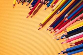 Volta ao conceito de escola. Lápis de cor em fundo laranja.