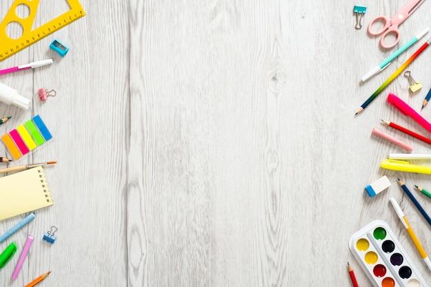 Volta ao conceito de escola, layout criativo com vários materiais escolares em fundo de madeira