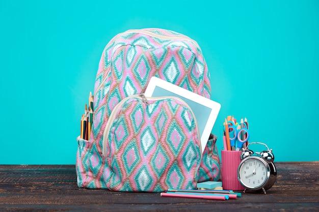 Volta ao conceito de escola. livros, lápis de cor e mochila em fundo azul
