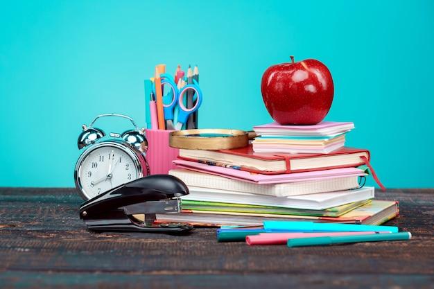 Volta ao conceito de escola. livros, lápis de cor e relógio sobre fundo azul