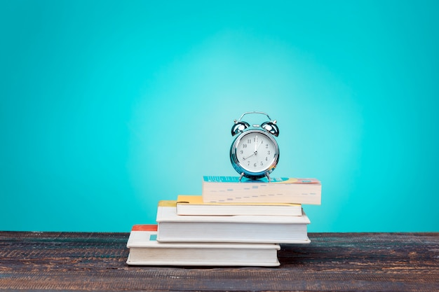 Volta ao conceito de escola. livros, lápis de cor e relógio
