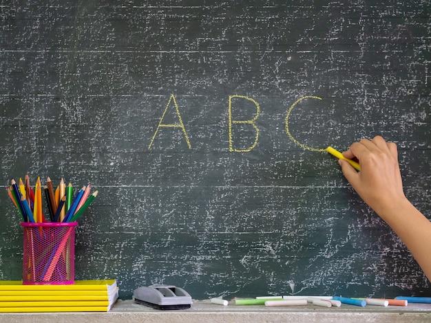 Volta ao conceito de escola. mão escrevendo no quadro-negro com papelaria na frente do blackbo