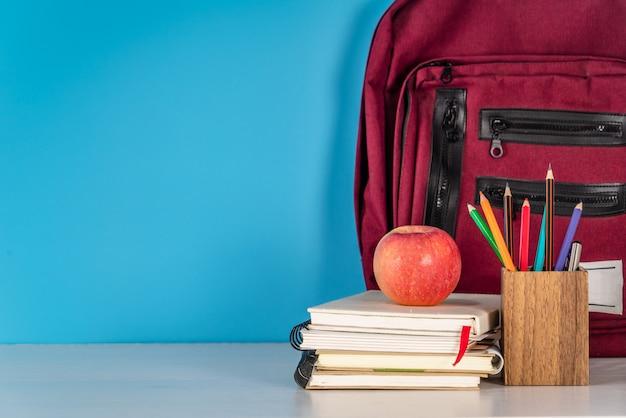 Volta ao conceito de escola. material escolar e maçã na mesa branca