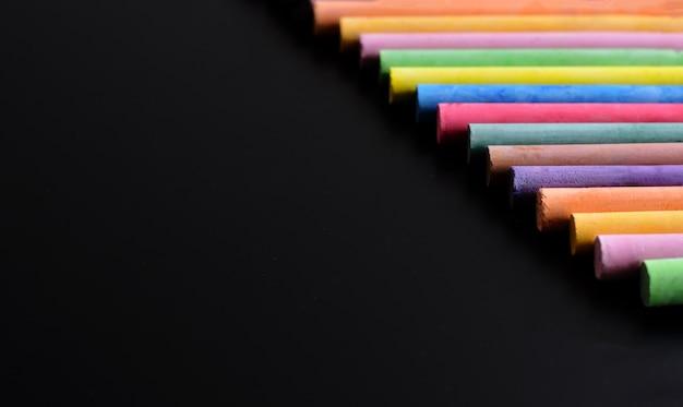 Volta ao conceito de escola ou faculdade, vista superior de gizes coloridos no quadro-negro