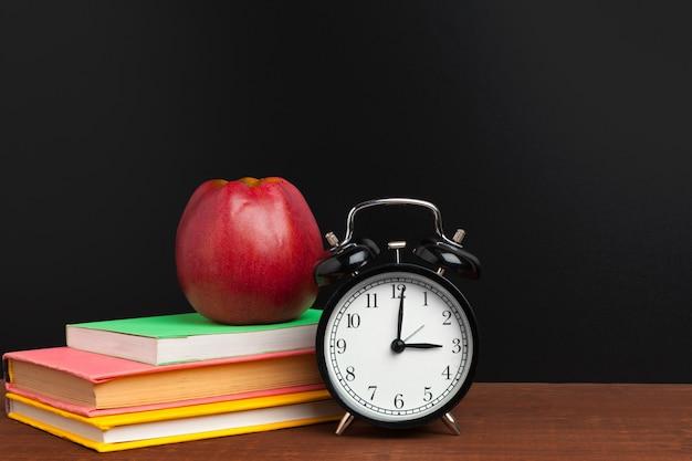 Volta ao conceito de escola. quadro-negro com livros e maçã na mesa de madeira