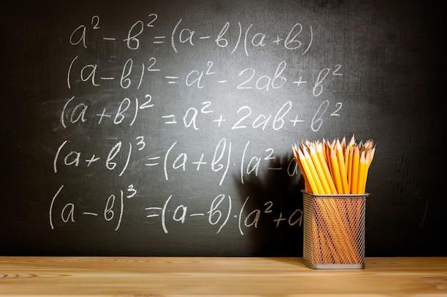Volta ao conceito de escola. schoolbooks velhos e lápis que encontram-se em uma mesa de madeira da escola na frente de um quadro preto com a escola das fórmulas matemáticas.