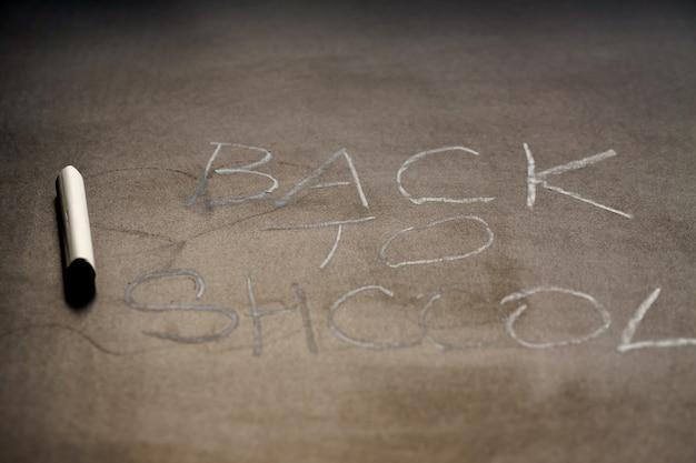 Volta ao conceito de escola. texto de giz branco na lousa de escola. profundidade superficial de campo
