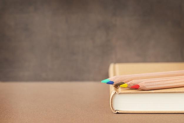 Volta às aulas e ao conceito de educação lápis de madeira coloful em um livro perto do quadro-negro e lugar para texto