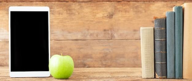 Volta às aulas e ao conceito de educação o tablet com tela preta e maçã verde de um lado e uma pilha de livros do outro lado em um fundo de madeira