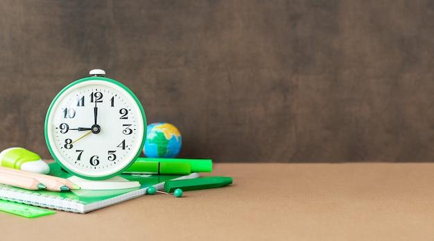 Volta às aulas e conceito de educação papelaria para estudos e relógio perto do quadro-negro e local para texto