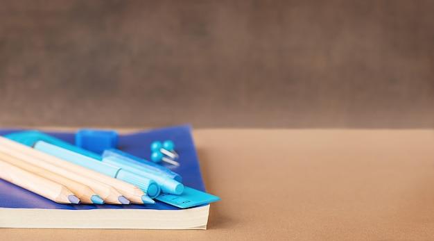 Volta às aulas e conceito de educação papelaria para estudos em fundo azul e lugar para texto