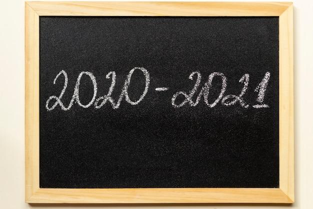 Volta às aulas e novo conceito de ano letivo. quadro-negro com texto 2020-2021 em moldura de madeira.