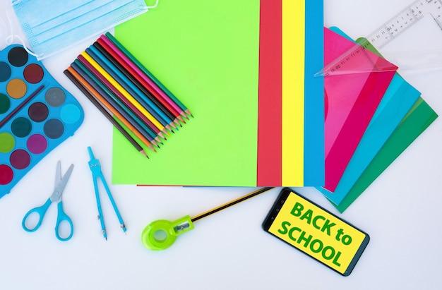 Volta às aulas - fundo colorido, lápis, cadernos, tesouras e acessórios - conceito de educação - mensagem no celular