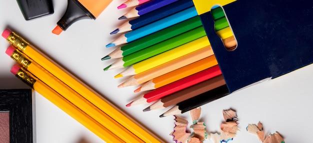 Volta às aulas, lápis de cor e um marcador rosa em uma mesa branca