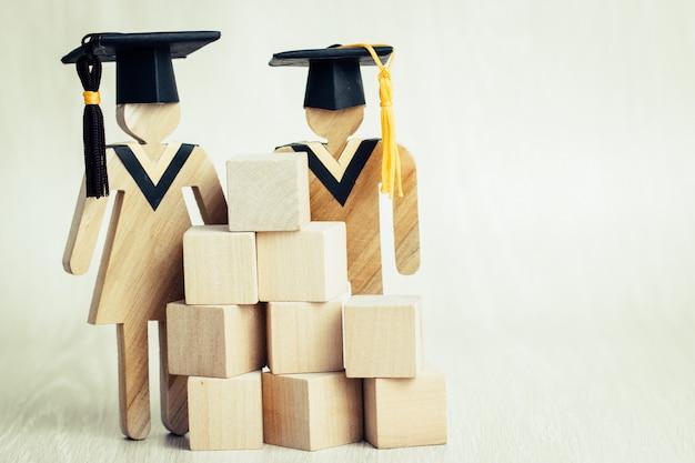 Volta para a escola, alunos cadastre-se madeira graduação comemorando boné com blocos quadrados de madeira