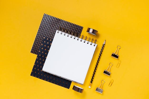 Volta para o conceito de escola, bloco de notas, estojo, papelaria e material escolar. parede horizontal superior copyspace vista amarela
