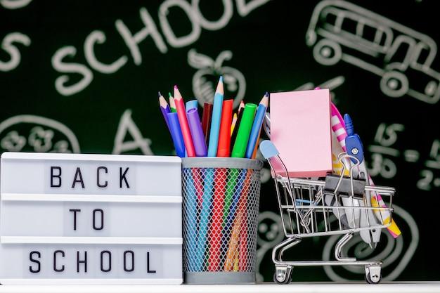Volta para o fundo da escola com livros, lápis e globo na mesa branca sobre um fundo verde lousa.