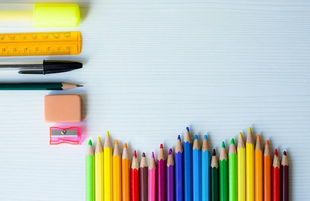 Volta para o quadro de escola com arco-íris de canetas coloridas e outros materiais escolares e fundo de madeira branco