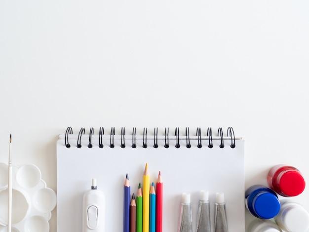 Voltar ao conceito de escola e artista garoto conceito com livro de desenho, giz de cera, lápis de cor, cor de cartaz e papelaria escolar o