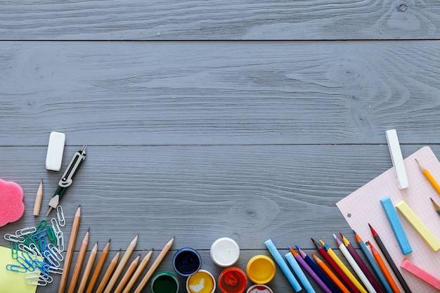 Voltar ao conceito de plano de fundo da escola com espaço de cópia gratuita para texto, papelaria moderna suprimentos, lápis de cor, tintas, papel na mesa de madeira cinza escura, ensino fundamental moderno, vista superior