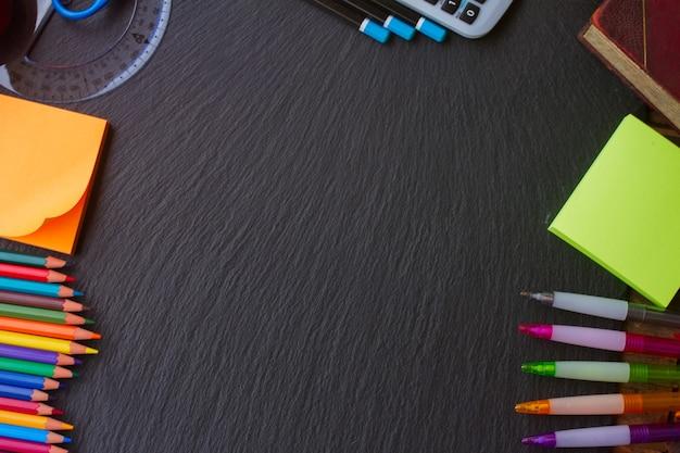 Voltar ao material escolar - anotações, lápis e canetas como uma moldura no quadro-negro